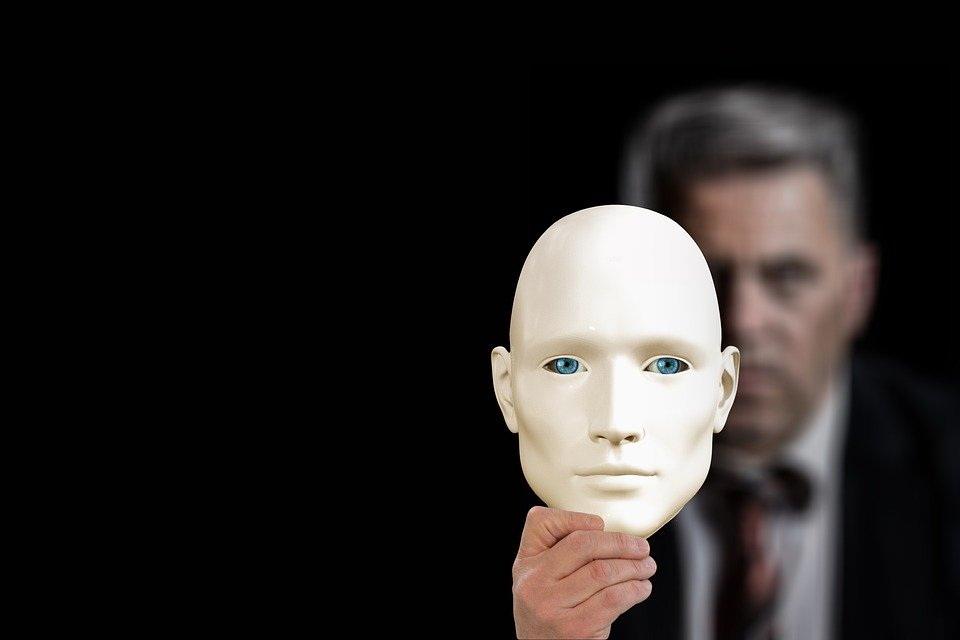 This image shows a man holding a mask. It illustrates that social skills training teaches Autistic kids to mask and hide who they are